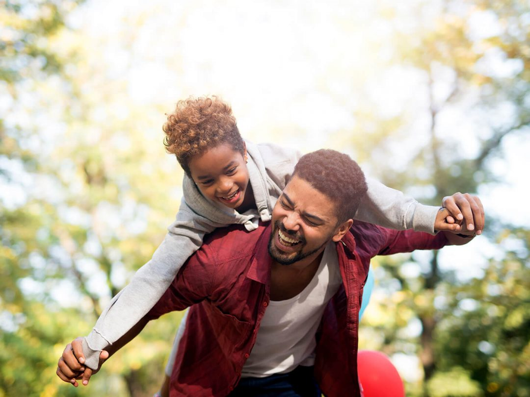 father-holding-his-daughter-on-shoulders-and-laughing